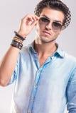 Hombre casual de la moda que saca sus gafas de sol Fotos de archivo libres de regalías