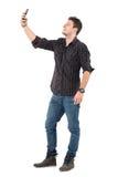 Hombre casual en vaqueros y la camisa de tela escocesa que toma las fotos con el teléfono móvil imagenes de archivo