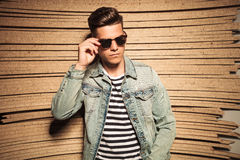 Hombre casual joven fresco que saca sus gafas de sol Imagen de archivo libre de regalías