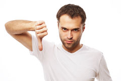 Hombre casual joven que hace los pulgares abajo Imagen de archivo libre de regalías