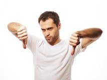 Hombre casual joven que hace los pulgares abajo Imagen de archivo