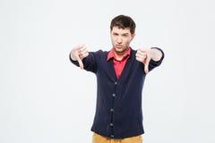 Hombre casual joven que muestra los pulgares abajo Imagen de archivo libre de regalías