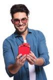 Hombre casual joven que presenta un pequeño regalo rojo Foto de archivo libre de regalías