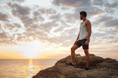 Hombre casual joven que se coloca en la roca de la montaña Fotos de archivo