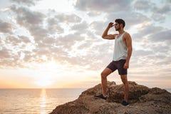 Hombre casual joven que se coloca en la roca de la montaña Imágenes de archivo libres de regalías