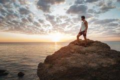 Hombre casual joven que se coloca en la roca de la montaña Imagen de archivo