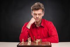 Hombre casual joven que se sienta sobre ajedrez Fotografía de archivo libre de regalías