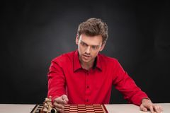 Hombre casual joven que se sienta sobre ajedrez Imagen de archivo
