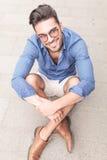 Hombre casual joven sonriente con los vidrios que se sientan en la acera Fotografía de archivo