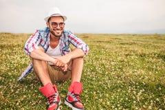 Hombre casual joven sonriente que se sienta en un campo Imagenes de archivo