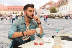 Hombre casual pensativo que toma un descanso para tomar café mientras que se sienta fotos de archivo