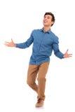 Hombre casual que camina que da la bienvenida y que parece para arriba sorprendido Imagenes de archivo