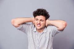 Hombre casual que cubre sus oídos Imagenes de archivo