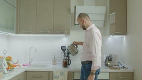 Hombre casual que hace té en cocina nacional metrajes