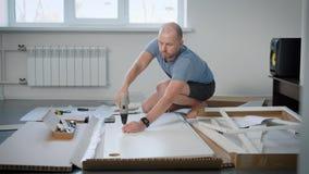 Hombre casual que lleva la camiseta azul y los pantalones cortos negros que montan la nueva tabla para su plano almacen de metraje de vídeo