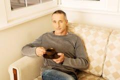 Hombre casual que se sienta en el café de consumición del sofá Foto de archivo