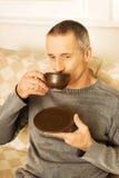 Hombre casual que se sienta en el café de consumición del sofá Imagenes de archivo