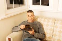 Hombre casual que se sienta en el café de consumición del sofá Fotos de archivo libres de regalías