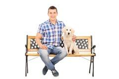 Hombre casual que se sienta en un banco con un perrito Fotografía de archivo libre de regalías