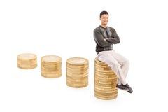 Hombre casual que se sienta en una pila de monedas Foto de archivo libre de regalías