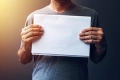 Hombre casual que sostiene el papel en blanco A4 como espacio de la copia Imagen de archivo libre de regalías