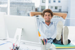 Hombre casual relajado con las piernas en el escritorio en oficina brillante Fotografía de archivo libre de regalías