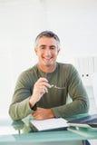 Hombre casual sonriente que sostiene sus vidrios Imagen de archivo