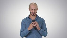 Hombre casual usando el teléfono de Smart de la célula que escribe el mensaje en fondo de la pendiente almacen de metraje de vídeo