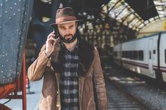 Hombre caucásico adulto barbudo atractivo que sostiene el teléfono elegante en su mano y que llama mientras que él que se coloca  Imagen de archivo