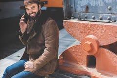 Hombre caucásico adulto barbudo atractivo que sostiene el teléfono elegante en su mano y que llama mientras que él que se coloca  Fotografía de archivo