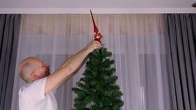 Hombre caucásico adulto que adorna el árbol de navidad - colocación del primero rojo de oro encima de árbol Decoración artificial almacen de metraje de vídeo