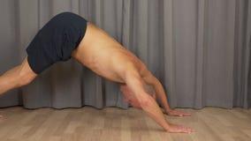 Hombre caucásico adulto que hace ejercicio del gato de la yoga en la sala de estar dentro Tiro bloqueado del perfil almacen de video