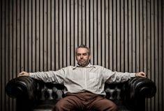 Hombre caucásico adulto que se sienta en el retrato del sofá del vintage Espacio de la copia de la escritura y pared de madera, E Imagen de archivo