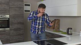 Hombre caucásico alegre con un café de consumición de la mañana de la barba en una cocina moderna y tomar un selfie, cámara lenta metrajes