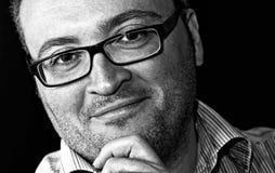 Hombre caucásico barbudo con gafas sonriente del tiro monocromático imágenes de archivo libres de regalías