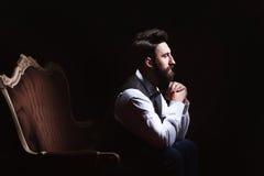 Hombre caucásico barbudo hermoso joven que se sienta en el sofá del vintage Piel y peinado perfectos Chaleco que lleva, camisa bl fotos de archivo