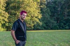 Hombre caucásico blanco que sonríe en la cámara Mirada alternativa diversa con el pelo rosado imagenes de archivo
