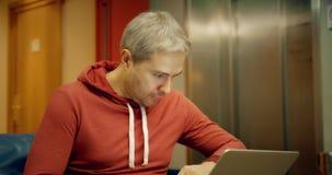 Hombre caucásico cabelludo gris en ropa casual usando su ordenador portátil en el vestíbulo del hotel almacen de metraje de vídeo