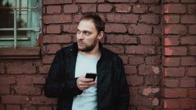 Hombre caucásico casual que usa smartphone afuera El mandar un SMS masculino joven barbudo hermoso del hombre de negocios Pared d metrajes