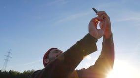 Hombre caucásico del inconformista de la raza mixta joven que hace Selfie en la puesta del sol hermosa en el lago Pescador Using  almacen de video