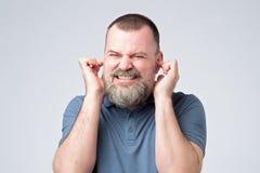 Hombre caucásico enfadado evitar para oír la preocupación de fuerte ruido fotos de archivo libres de regalías