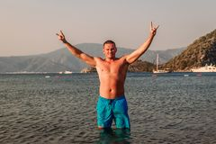 Hombre caucásico feliz en los pantalones cortos azules de la nadada que se colocan en un mar de manos para arriba en el aire fotos de archivo