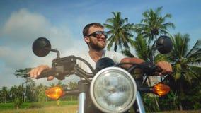 Hombre caucásico feliz joven que se sienta en la moto almacen de metraje de vídeo
