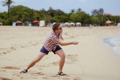 Hombre caucásico feliz que juega en piedras que lanzan de la playa en el océano, Bali Imagen de archivo