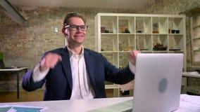 Hombre caucásico gozado que demuestra gesto del ganador mientras que se sienta en su lugar de trabajo cerca del ordenador portáti almacen de video