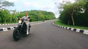 Hombre caucásico hermoso que disfruta de paseo de la moto almacen de video
