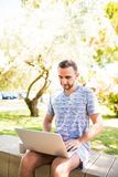 Hombre caucásico hermoso que usa sentarse del ordenador portátil al aire libre en un parque Día de la sol del verano Concepto de  fotos de archivo libres de regalías
