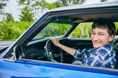 Hombre caucásico joven alegre que se sienta en su coche Fotos de archivo libres de regalías