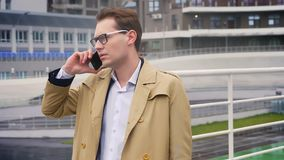 Hombre caucásico joven atractivo que tiene una conversación sobre el teléfono que hace una pausa el estadio en un serio y concent metrajes