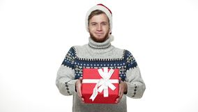 Hombre caucásico joven a cámara lenta que da el regalo de la Navidad de la sorpresa a la cámara almacen de video